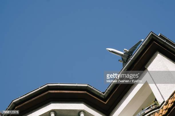Low Angle View Of Airplane Flying Over Building Against Clear Sky