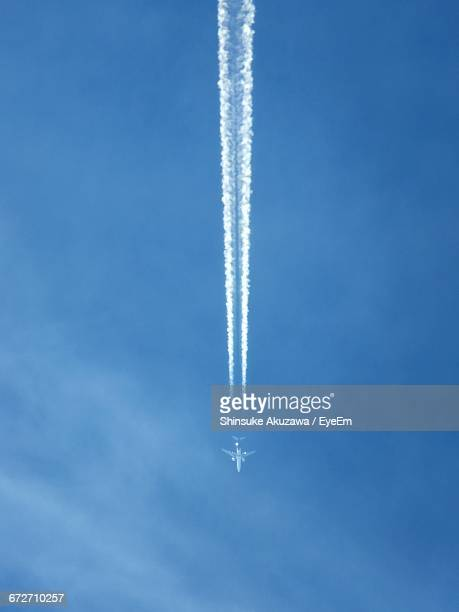 Low Angle View Of Airplane Flying With Vapor Trail Against Blue Sky