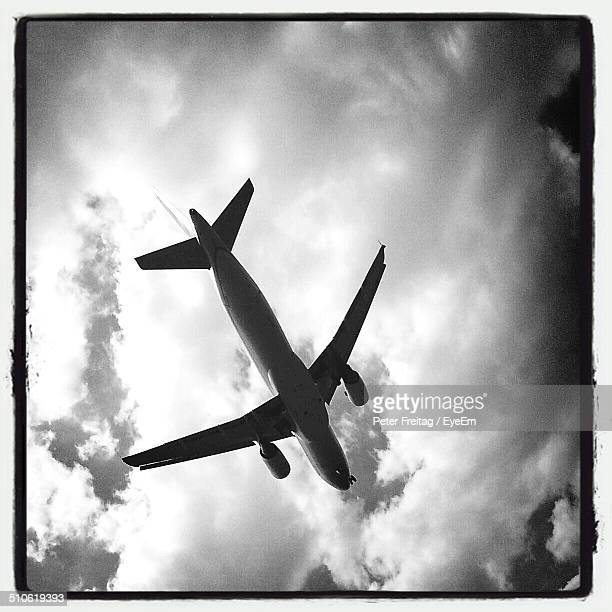 Low angle view of airplane in flight against clouds