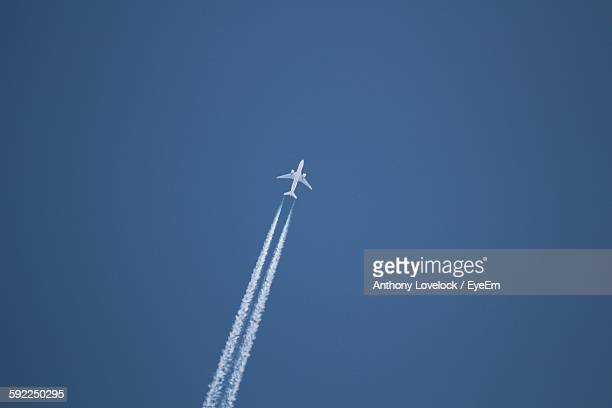 Low Angle View Of Airplane With Vapor Trail In Clear Blue Sky