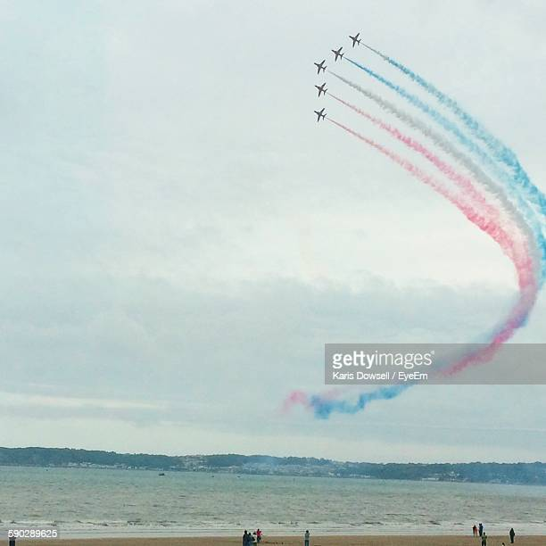 Low Angle View Of Airshow Forming Multi Colored Vapor Trail Over Beach
