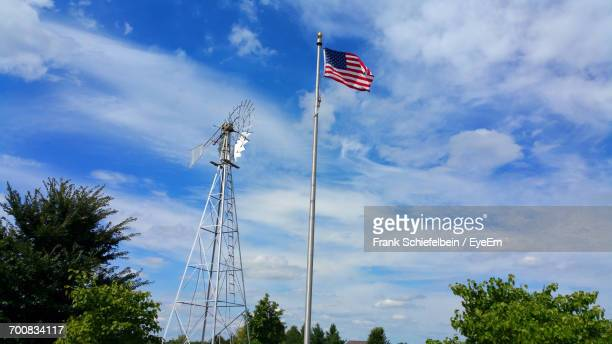 Low Angle View Of American Flag And Windmill Against Blue Sky
