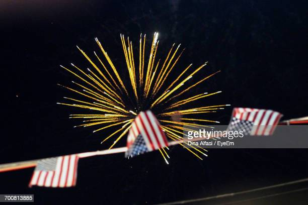 Low Angle View Of American Flag Buntings Against Firework Display At Night