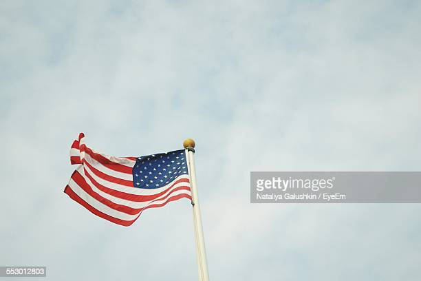 Low Angle View Of American Flag Fluttering Against Sky