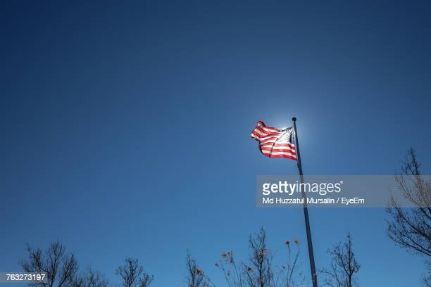 Low Angle View Of American Flag Waving Against Clear Blue Sky