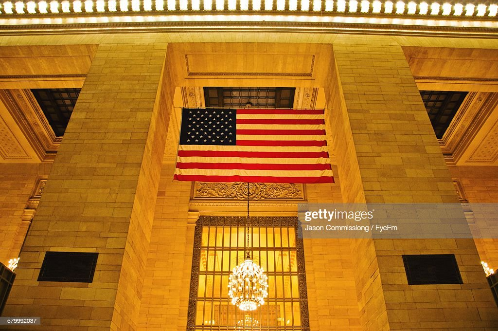 Low Angle View Of American Flag With Illuminated Chandelier In Grand Central Station