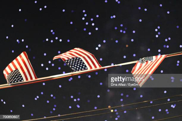 Low Angle View Of American Flags Hanging Against Firework Display At Night