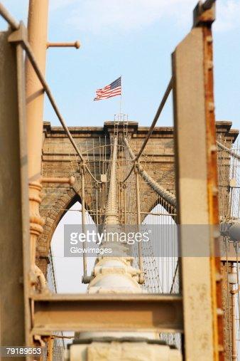 Low angle view of an American flag on a bridge, Brooklyn Bridge, New York City, New York State, USA : Stock Photo