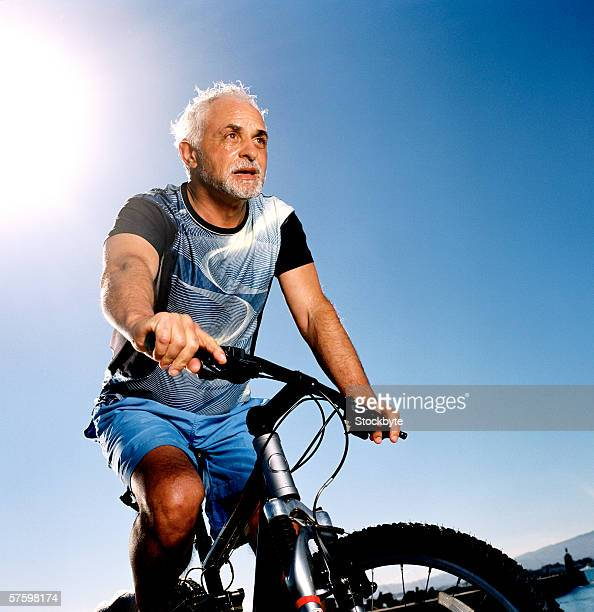 Low angle view of an elderly man cycling