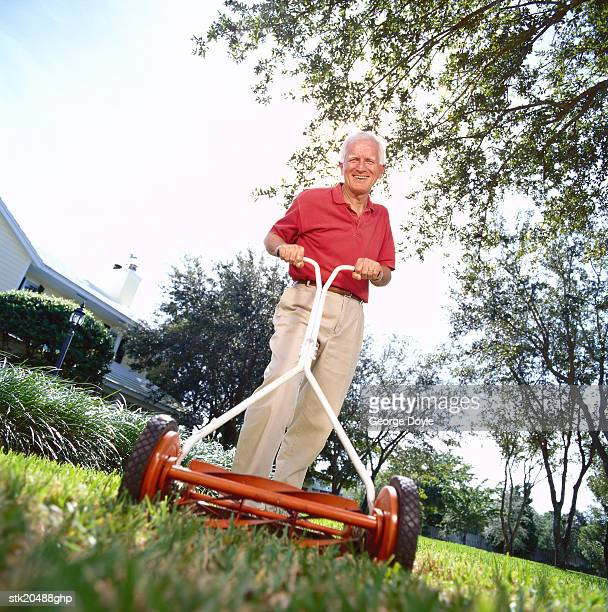 low angle view of an elderly man mowing the lawn with a mower