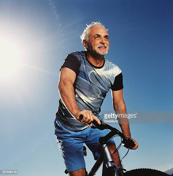 low angle view of an elderly man riding a bicycle