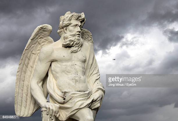 Low Angle View Of Angel Sculpture At Herrenhausen Gardens Against Cloudy Sky