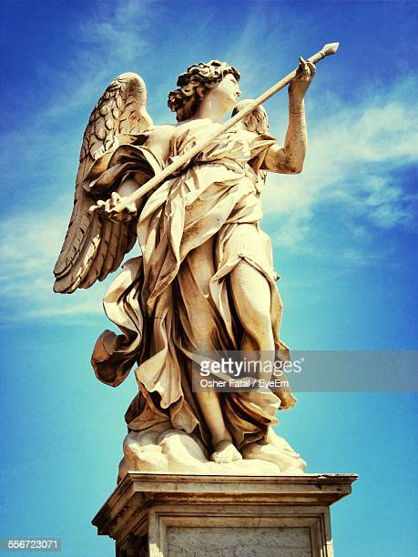Low Angle View Of Angel Statue On Ponte Sant Angelo Against Blue Sky