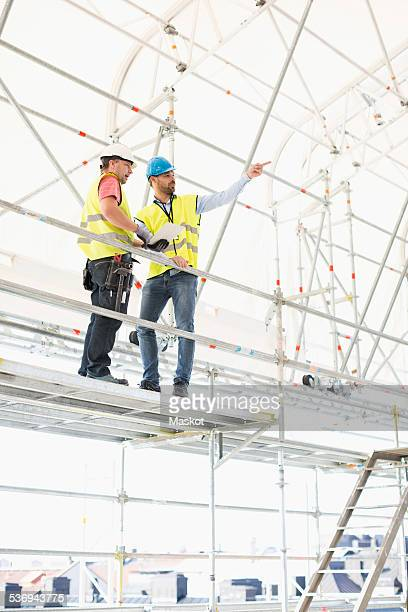 Low angle view of architect explaining plan to worker at construction site
