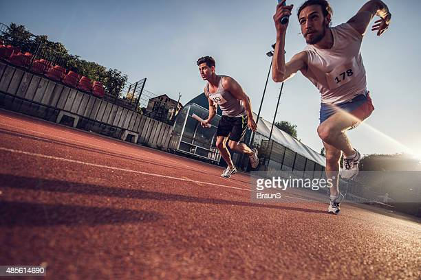 Low angle view of athletes on a relay race.
