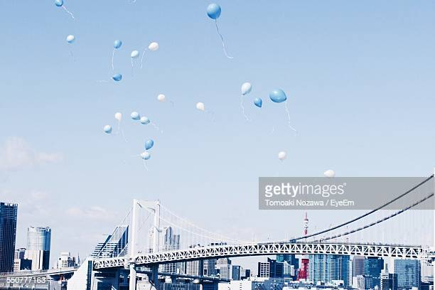 Low Angle View Of Balloons Flying Above Rainbow Bridge Against Clear Sky