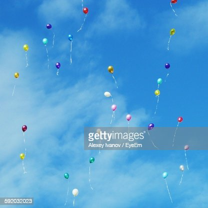Low Angle View Of Balloons Flying Against Sky : Stock Photo
