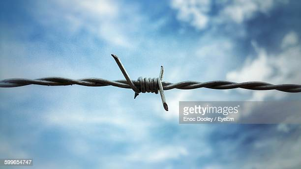 Low Angle View Of Barbed Wire Against Cloudy Sky