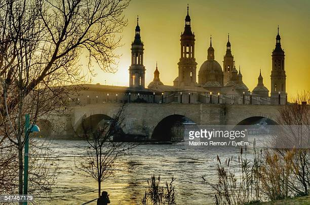 Low Angle View Of Basilica Of Our Lady Of The Pillar And Bridge Over River During Sunset