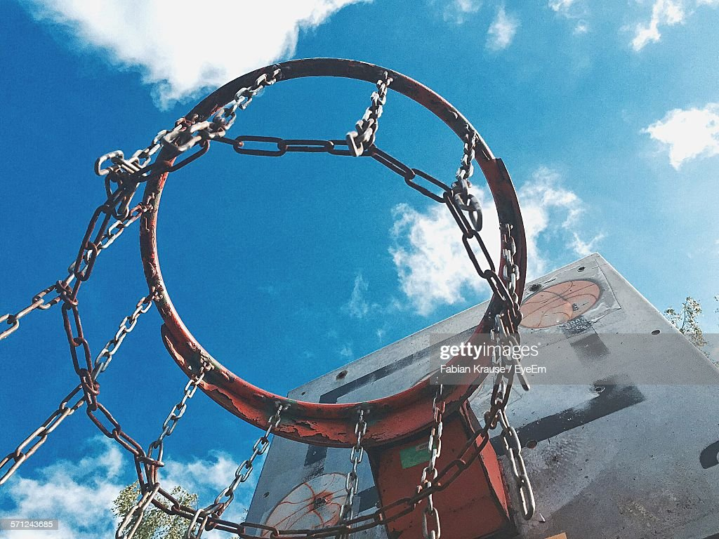 low angle view of basketball hoop against blue sky stock photo