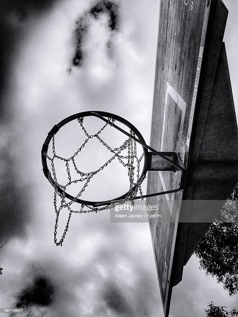 low angle view of basketball hoop against clouds stock photo