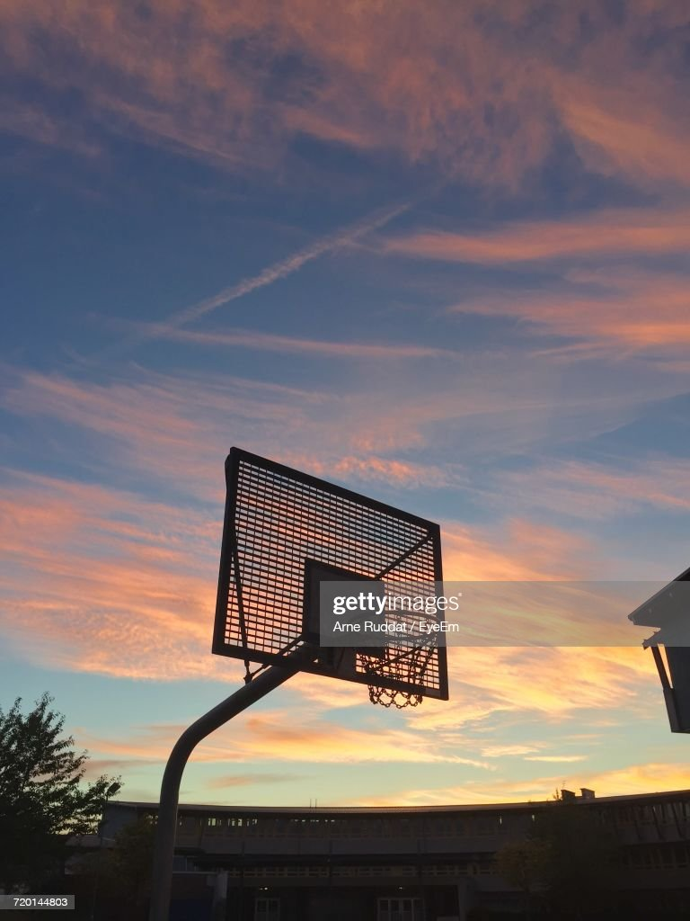 low angle view of basketball hoop against sky at sunset stock