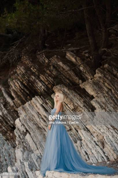 Low Angle View Of Beautiful Bride Standing Against Mountain