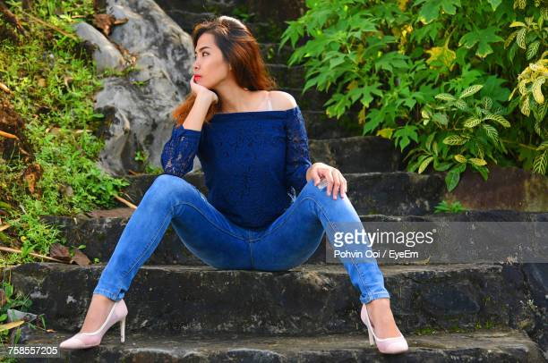 Low Angle View Of Beautiful Woman Looking Away While Sitting On Steps At Park