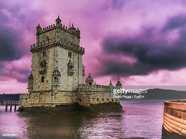 Low Angle View Of Belem Tower Amidst River Against Cloudy Sky At Dusk
