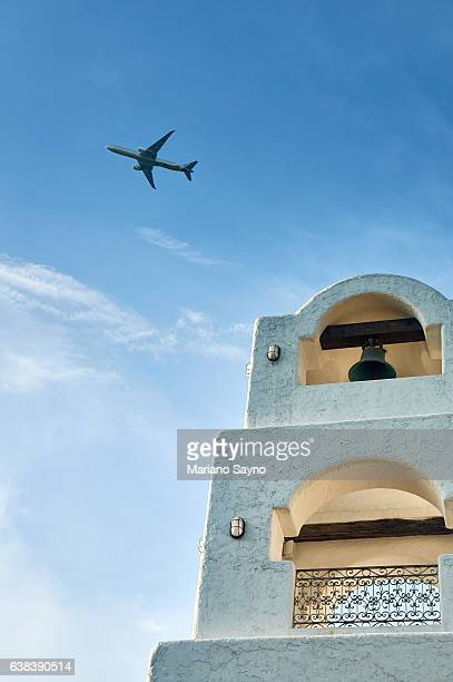 Low angle view of bell tower with plane flying in sky above