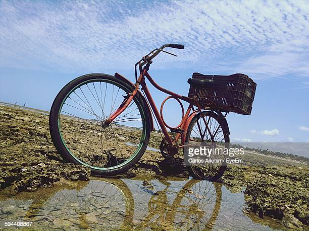 Low Angle View Of Bicycle At Beach Against Sky