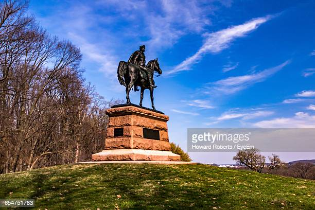Low Angle View Of Black Human And Animal Statue Against Blue Sky At Valley Forge National Park