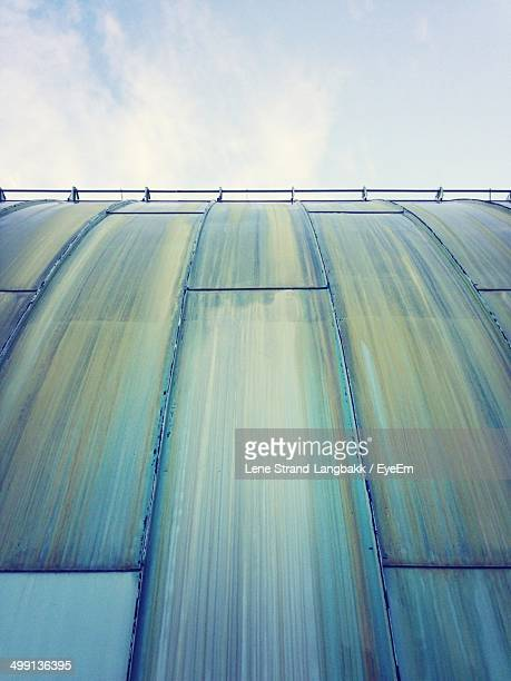 Low angle view of blue wall with railing against the sky