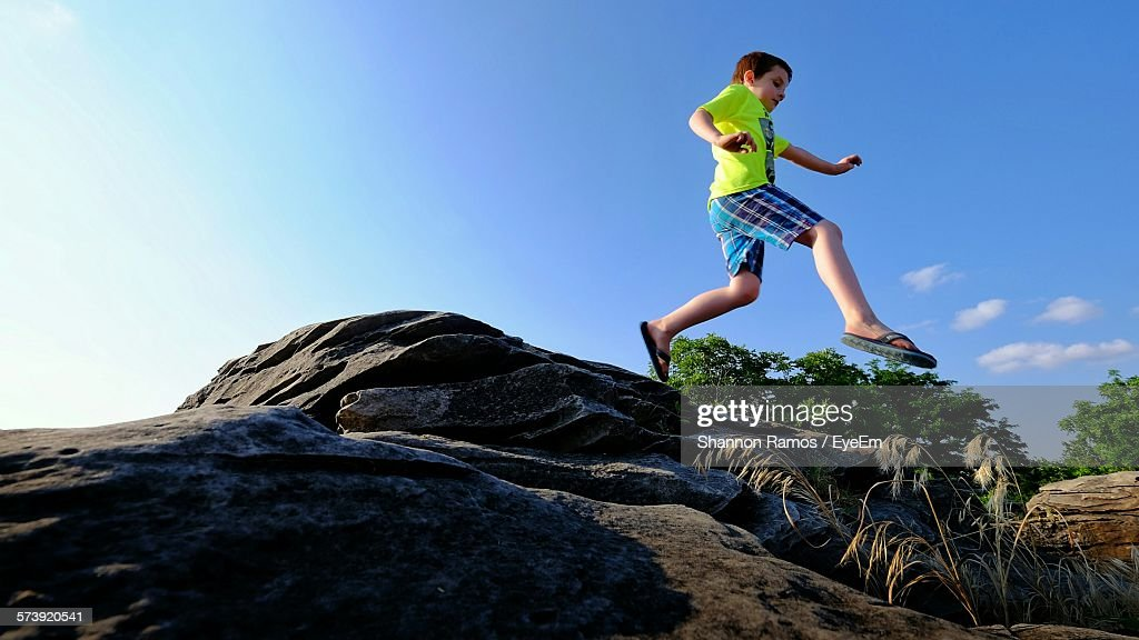 Low Angle View Of Boy Jumping In Rock City Park : Stock Photo
