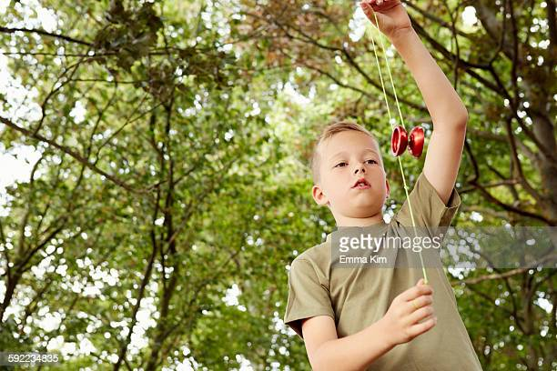 Low angle view of boy playing with yo-yo looking down
