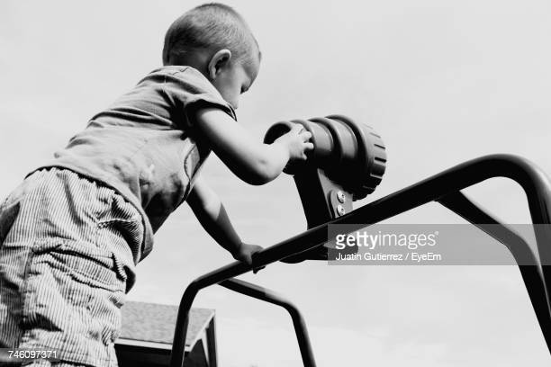 Low Angle View Of Boy Using Hand-Held Telescope Against Sky