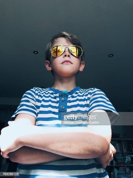Low Angle View Of Boy Wearing Sunglasses While Standing At Home