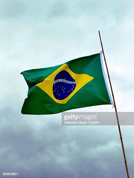 Low angle view of Brazilian flag fluttering against clouds