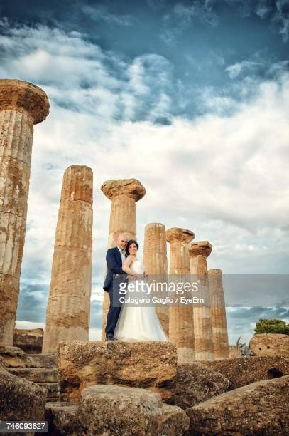 Low Angle View Of Bride And Groom By Old Ruin Columns Standing Against Cloudy Sky