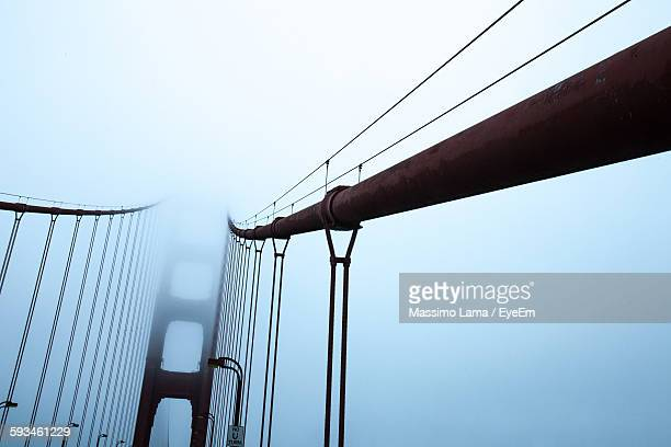 Low Angle View Of Bridge Cables Against Sky During Foggy Weather