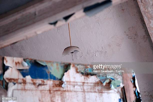 Low Angle View Of Broken Pendant Light In Abandoned House