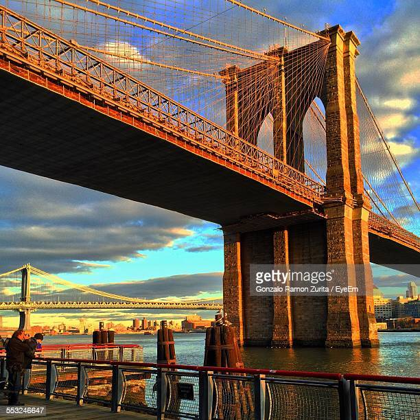 Low Angle View Of Brooklyn Bridge Against Cloudy Sky At Sunset