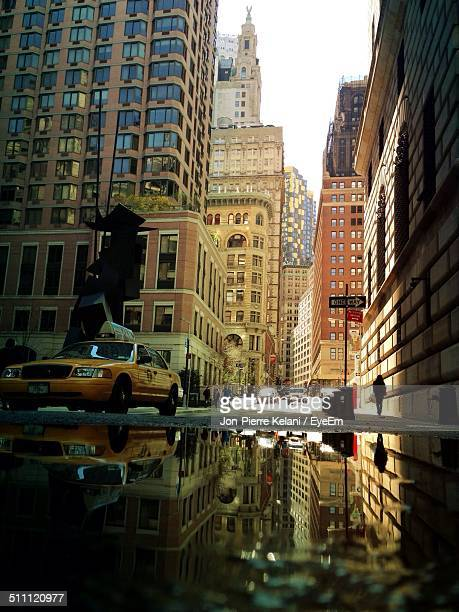 Low angle view of buildings and cars with puddle on foreground