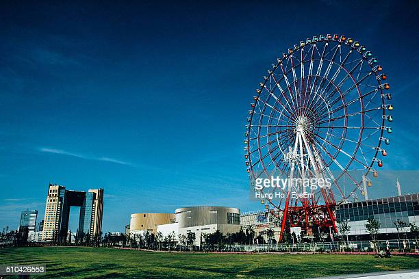 Low angle view of buildings and Ferris wheel against blue sky