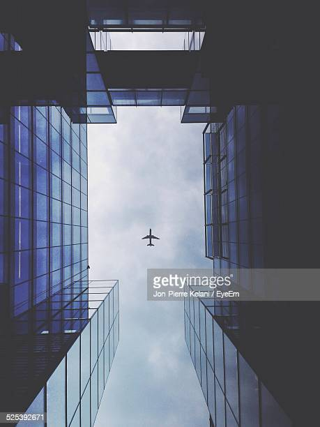 Low Angle View of Buildings And Plane In Sky