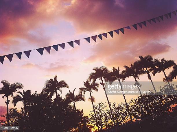 Low Angle View Of Bunting Flags And Silhouette Trees At Sunset