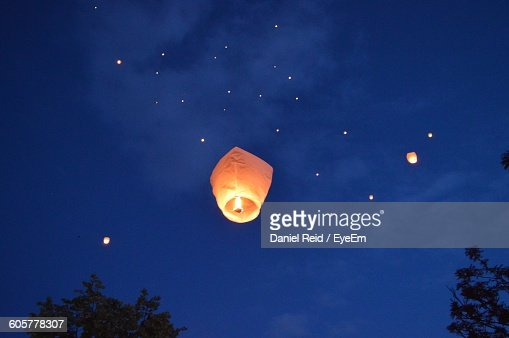 Low Angle View Of Burning Sky Lanterns Against Sky At Night