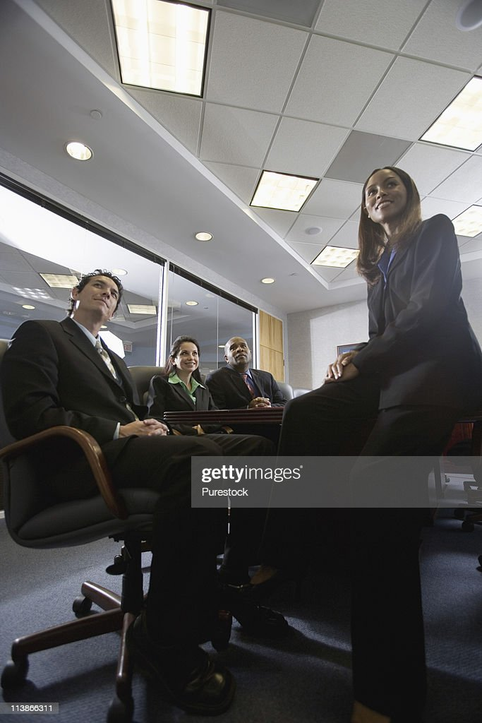 Low angle view of business men and women at a presentation in a formal conference room : Stock Photo