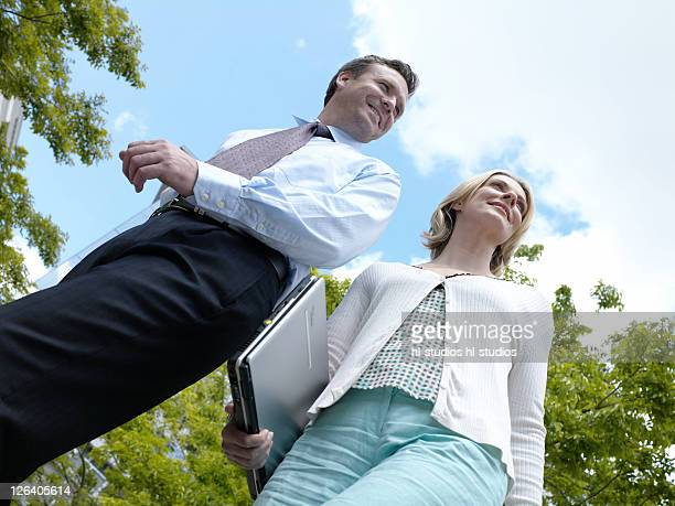 Low angle view of businessman and businesswoman smiling