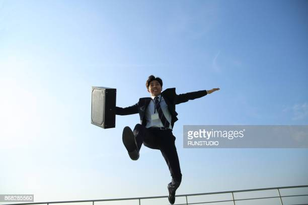 Low angle view of businessman jumping with briefcase